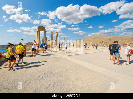 Tourists enjoy late afternoon views of the Mediterranean sea from the ancient ruins of the Lindos, Acropolis on the island of Rhodes, Greece - Stock Photo