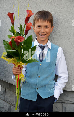 Boy with flowers September 1 goes to school - Stock Photo