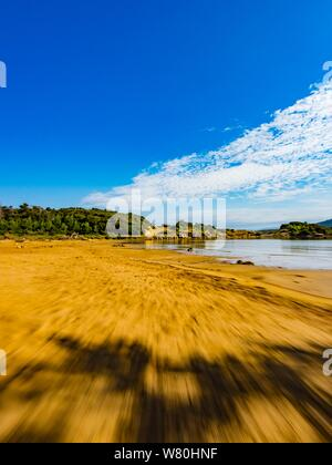 Sandy beach vacated vacant countryside speeding low view along - Stock Photo