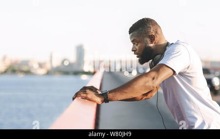 Tired young black man leaning on the bridge - Stock Photo