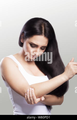 Pain in the elbow. A woman suffering from chronic severe rheumatism. Construction of pain in the elbow and treatment. Painful sensations. The concept - Stock Photo