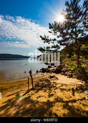 Sandy beach vacated vacant countryside speeding against sun - Stock Photo
