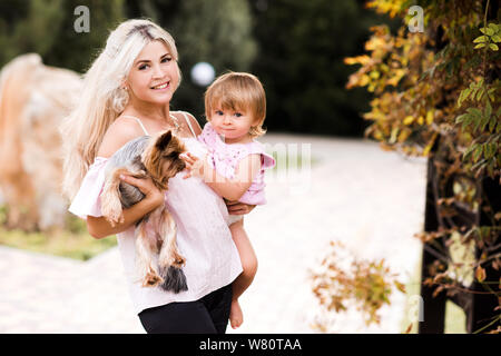 Happy mother holding baby 1 year old daughter and small pet dog outdoors over nature background in park. Looking at camera. Motherhood. Maternity. - Stock Photo