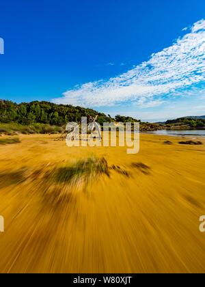 Sandy beach vacated vacant countryside speeding low view along wooden framework focused in center in distance - Stock Photo