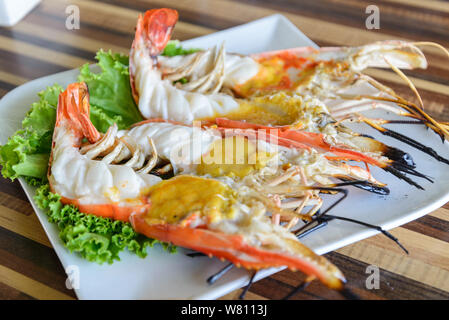 Cutting half grilled giant river prawn, famous local Thai luxury fine dinning menu in Thailand, serve on white plate dish. - Stock Photo