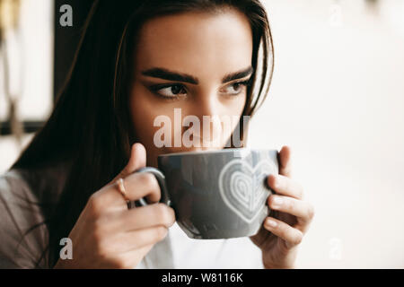 Close up portrait of a lovely young woman drinking coffee in coffee shop near a window and looking away seriously. - Stock Photo