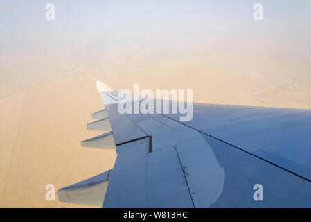 Blurry unclear sky above desert earth surface at troposphere atmosphere viewed from airplane's window located above airplane's wing and jet. - Stock Photo