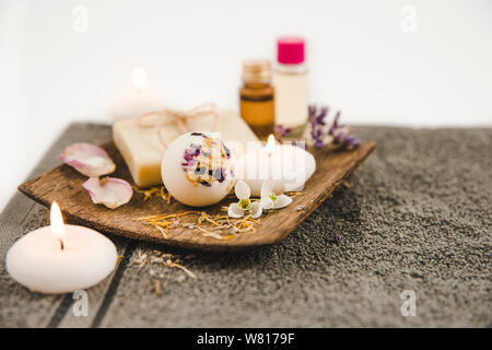 Various spa bath products on brown wooden tray creamy bath bomb, natural soap bar with cotton string, dried flower petals, spa candles lit, essential - Stock Photo