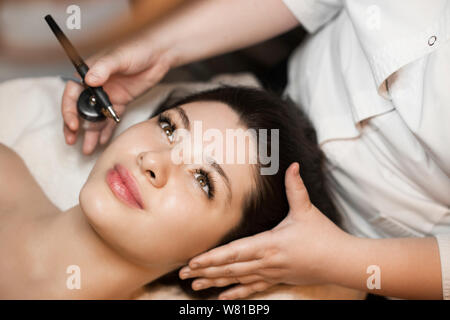 Close up of a lovely brunette having oxygen procedure on her face in a wellness spa salon. - Stock Photo