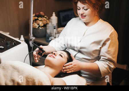 Lovely young female cosmetologist with red hair doing oxygen therapy on a female face in a spa salon. - Stock Photo
