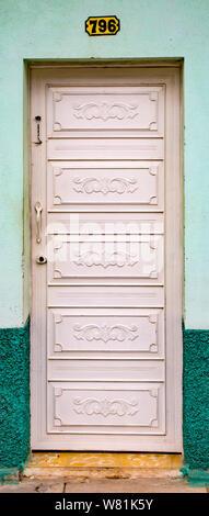 Trinidaad, Cuba Nov 26, 2017 - White door on green wall - Stock Photo