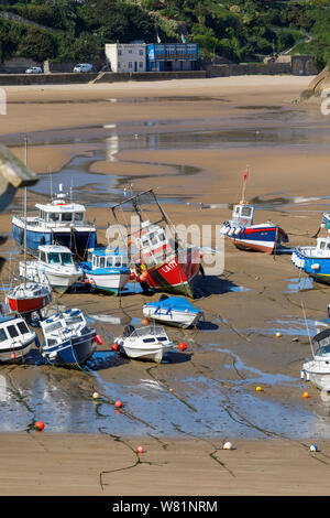 Fishing boats beached at low tide in the harbour at Tenby, a walled seaside town in Pembrokeshire, south Wales coast on the west of Carmarthen Bay - Stock Photo
