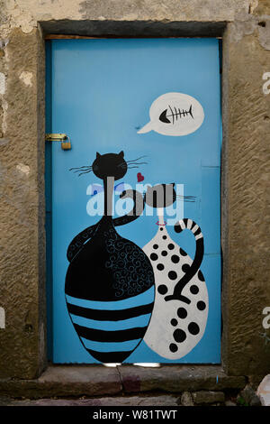 Two enamored hungry cats dreaming of fish. Painted door in Groznjan/ Grisignana, Istria, Croatia, Europe - Stock Photo