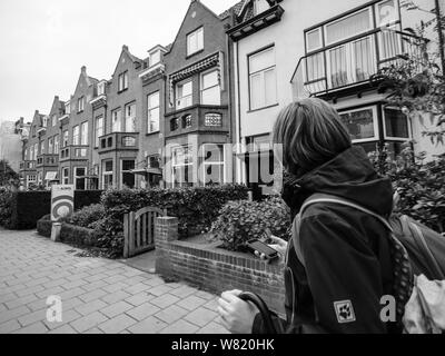 Haarlem, Netherlands - Aug 16, 2018: Rear view of woman with backpack walking on tiny street admiring Dutch architecture black and white - Stock Photo