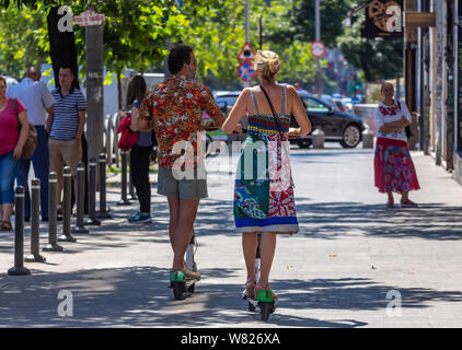 Bucharest, Romania - August 07, 2019: People ride Lime-S Electric Scooters on a sidewalk in downtown Bucharest, Romania. - Stock Photo