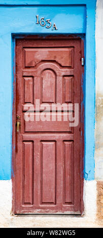 Trinidaad, Cuba Nov 26, 2017 - Red door on blue and white wall - Stock Photo