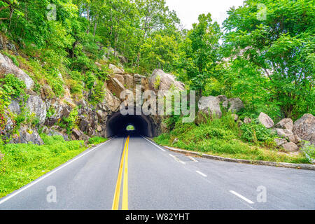 Tunnel through the rocks at skyline drive national park. The skyline drive is 105 miles long and runs along the blue ridge parkway in the appalachian - Stock Photo