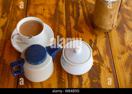 Traditional indian tea set with masala chai on wooden background. Composition from teapot, sugarbowl and cup on table. Top veiw. - Stock Photo