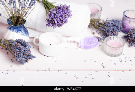 Spa massage setting, lavender product, salt, candles, soap on white background - Stock Photo