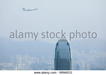 A Cathay Pacific Boeing 747-400 passenger jet flies over the International Finance Centre (IFC) to commemorate the retirement of the Boeing 747-400 ai - Stock Photo