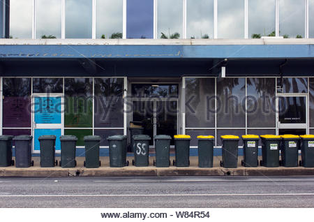 General garbage and recycling bins lined up for emptying on the footpath outside a city building in Australia. - Stock Photo