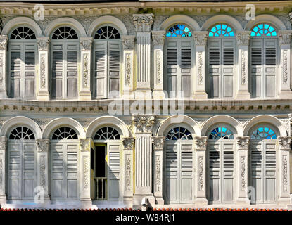 Front view of vintage traditional Singapore shop houses with ornate exteriors, antique louvered shutters and arched windows in historic Little India, - Stock Photo