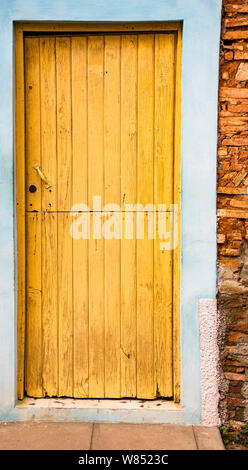 Trinidaad, Cuba Nov 26, 2017 - Yellow door on blue and brick wall - Stock Photo