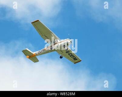 A Cessna 152 in flight and pictured against a blue sky