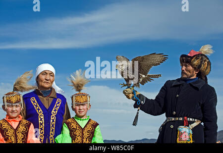 Kazakh hunter with Saker Falcon (Falco cherrug) at Eagle hunters festival near Ulgii, western Mongolia, October 2008. - Stock Photo