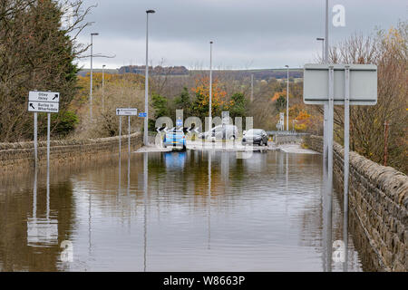 Flooding - flooded road is impassable to cars as deep flood water makes driving hazardous for vehicles - Burley In Wharfedale, Yorkshire, England, UK. - Stock Photo