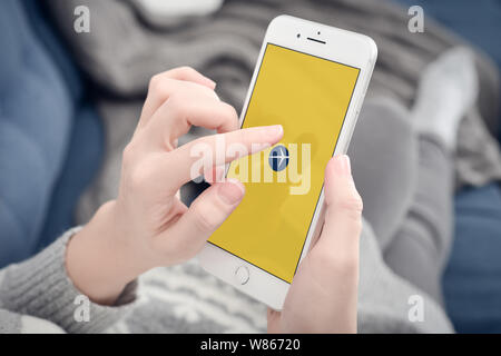 Kyiv, Ukraine - January 24, 2018: Woman using Expedia app on Apple iPhone 8 plus at home for search for airline tickets - Stock Photo