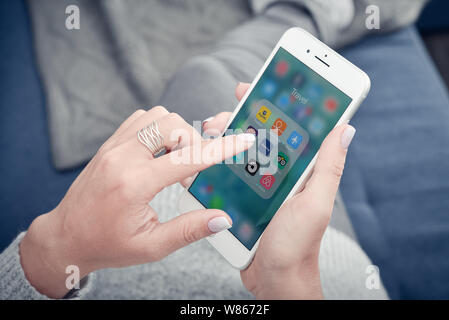Kyiv, Ukraine - January 24, 2018: Woman using travel apps on Apple iPhone 8 plus at home for planning trip. - Stock Photo