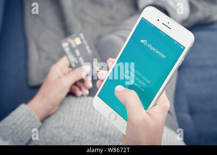Kyiv, Ukraine - January 24, 2018: Woman using skyscanner app on Apple iPhone 8 plus at home for search for airline tickets - Stock Photo