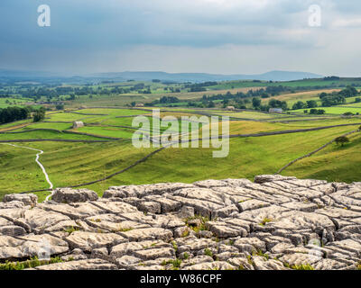 View over malhamdale from the limestone pavement above Malham Cove near Malham Yorkshire Dales National Park England - Stock Photo