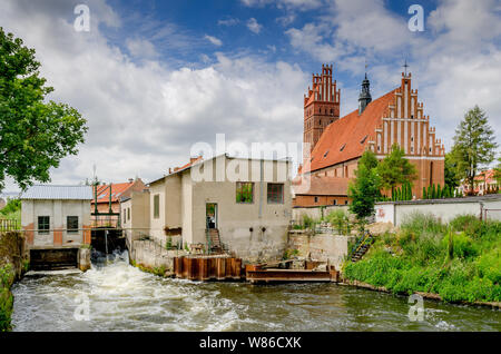 Dobre Miasto, ger. Guttstadt, warmian-mazurian province, Poland.  Small hydroelectric power plant. In the background - 14th cent.  collegiate church. - Stock Photo