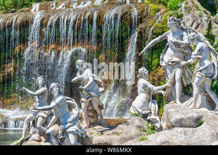 23 JUNE 2019 / CASERTA, ITALY: A group of statues in front of a waterfall  in the beautiful gardens of the Caserta Palace in Italy. - Stock Photo