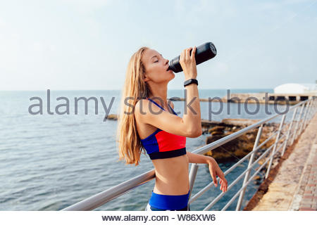 Side view of gorgeous sportswoman with long blonde hair drinking a water from bottle after workout outside, near the sea. - Stock Photo