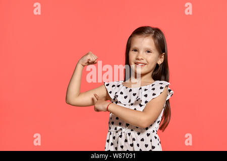Close-up studio shot of beautiful brunette little girl posing against a pink background. - Stock Photo
