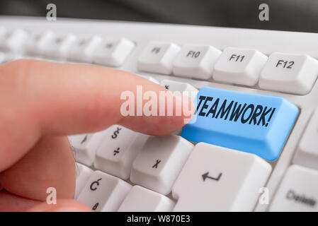 Writing note showing Teamwork. Business concept for combined action of group especially when effective and efficient White pc keyboard with note paper - Stock Photo