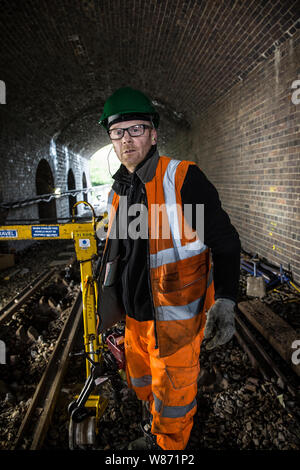 Maintenance team work on London Underground Central Line. Tack defect work grinding and skimming tracks, tamping and redistributing ballast. London UK - Stock Photo