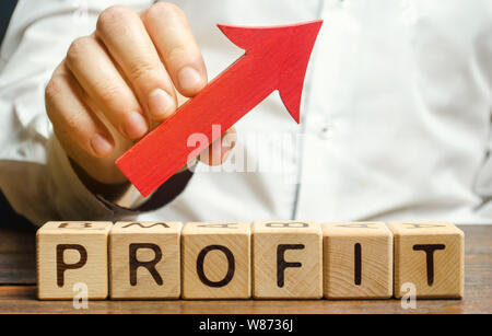 Wooden blocks with the word Profit and an up arrow. Concept of business success, financial growth and wealth. Increase profits and investment fund. Pe - Stock Photo