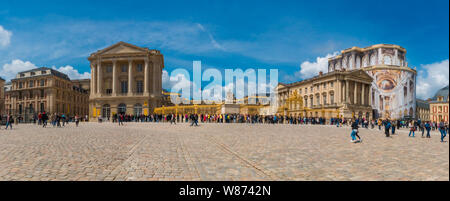 Lovely panorama picture of the Palace of Versailles in front of the golden royal gate at the entrance in the cobblestoned court of honour... - Stock Photo