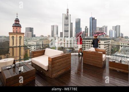 tourists in Frankfurt on a rainy day looking at the Frankfurt skyline from the   Galeria Kaufhof roof terrace, Frankfurt am Main, Germany - Stock Photo