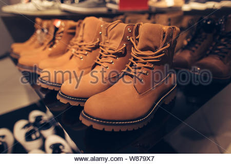 Men's winter boots. Men's winter brown boots in clothing store ready for sale - Stock Photo