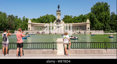 Horizontal panoramic of the boating lake and Monument to King Alfonso XII at Retiro Park in Madrid.