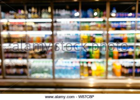 Bottles of beverages in fridge. Fridge with cold bottles of beverages on shelves in supermarket. Blurred background - Stock Photo