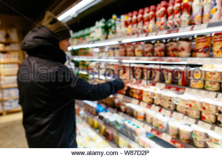 Shopping in supermarket. Man chooses yogurt in the fridge of milk department supermarket. Blurred photo - Stock Photo