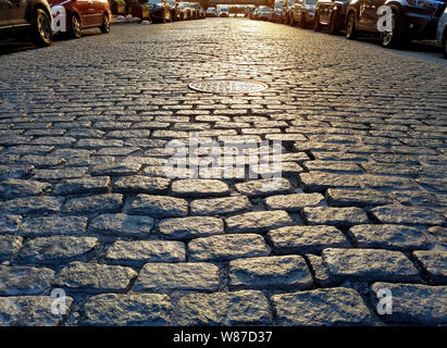 Sunlight shines on the cobblestones of Harrison Street in the Tribeca neighborhood of Manhattan in New York City NYC - Stock Photo