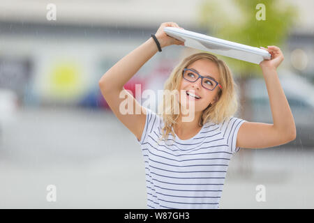 Beautiful young girl uses laptop as umbrella in hot summer day. - Stock Photo