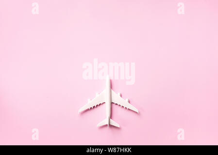 Top view of white model plane, airplane toy on pink pastel background. Flat lay with copy space. Trip or travel banner. - Stock Photo